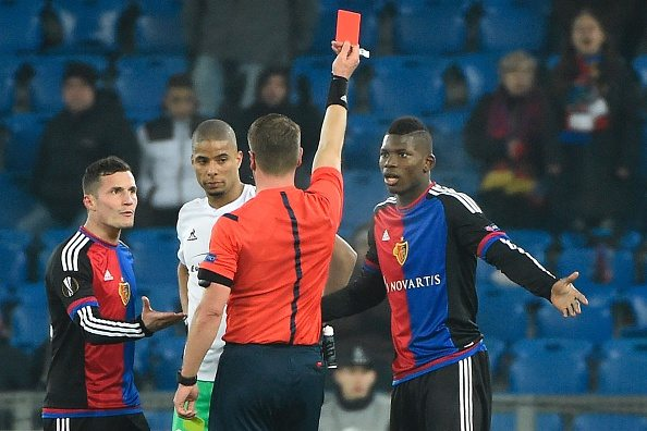 The referee shows a red card to Basel's Swiss forward Breel Embolo (R) next to Basel's Swiss midfielder Taulant Xhaka (L) and St Etienne's French forward Kevin Monnet-Paquet (C) during the UEFA Europa League round of 32 second leg football match between FC Basel and Saint-Etienne at the St Jakob Stadium, on February 25, 2016 in Basel. / AFP / OLIVIER MORIN (Photo credit should read OLIVIER MORIN/AFP/Getty Images)