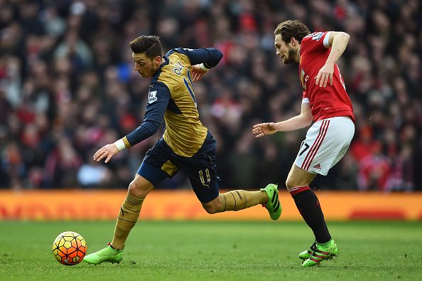 MANCHESTER, ENGLAND - FEBRUARY 28: Mesut Oezil of Arsenal goes past Daley Blind of Manchester United during the Barclays Premier League match between Manchester United and Arsenal at Old Trafford on February 28, 2016 in Manchester, England. (Photo by Laurence Griffiths/Getty Images)